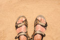 Feet in sandals on sand Royalty Free Stock Photo