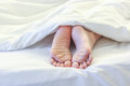 Feet of sleeping woman in white bed room Royalty Free Stock Photo