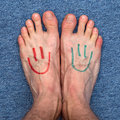 Feet smileys legs with smiley faces on the carpet Stock Photos