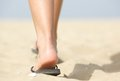 Feet walking in flip flops on beach close up low angle Stock Photography
