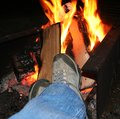Feet warming at a camp fire Stock Photo