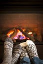 Feet warming by fireplace in wool socks cozy fire Royalty Free Stock Photography