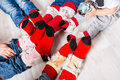 Feet wearing Christmas socks on wood floor. Happy family at home. Xmas holidays concept Royalty Free Stock Photo