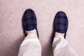 Feet wearing slippers on carpet Royalty Free Stock Photo