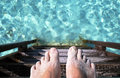 Feet on wooden ladder leading into the sea front part of Royalty Free Stock Photos