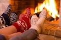 Feet in wool socks near fireplace in winter Royalty Free Stock Photo