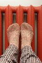 Feet with wool socks warming on the radiator Royalty Free Stock Images