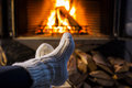 Feet in woolen socks by fireplace. Woman sitting at a cosy fire warming her cold feet.