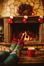 Feet in woollen socks by the christmas fireplace woman relaxes warm fire with a cup of hot drink and warming up her Royalty Free Stock Images