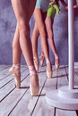 The feet of a young ballerinas in pointe shoes close up three against background wooden floor Royalty Free Stock Photography