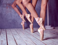 The feet of a young ballerinas in pointe shoes close up three against background wooden floor Royalty Free Stock Photo