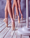 The feet of a young ballerinas in pointe shoes close up three against background wooden floor Stock Image