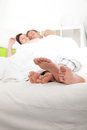 Feet of a young couple sleeping in bed view from the bottom the the bare sticking out from under the bedclothes Royalty Free Stock Photos