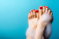 Feet of a young girl with red nails with drops of cream scrub and coffee beans around on a blue Royalty Free Stock Photo