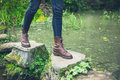 Feet of young person on stepping stones in a pond. Royalty Free Stock Photo