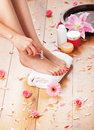 Feet of a young woman on a shaving procedure sexy the image is taken background with flowers and towel Royalty Free Stock Image