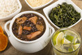 Feijoada brazilian beef sausage pork and black bean stew served with manioc flour kale white rice and oranges caipirinha on the Stock Photos