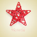 Feliz navidad merry christmas in spanish a red star and the sentence written on a beige background with a retro effect Royalty Free Stock Photo