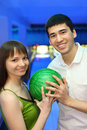 Fellow and girl turned to each other and hold ball