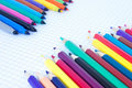 The felt pens and pencils placed diagonally on sheet with cells Royalty Free Stock Image