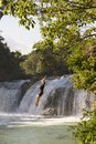 Adventure Traveller Jumping Off Waterfall In Belize