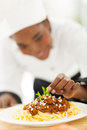 Female african cook garnishing spaghetti in modern kitchen Royalty Free Stock Image