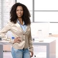 Female afro officeworker posing at office desk worker for portrait smiling Stock Photo