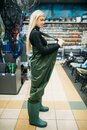 Female angler in rubber jumpsuit, fishing shop Royalty Free Stock Photo