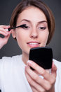 Female applying make-up Stock Images