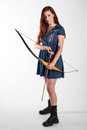 Female archer in combat boots a young with her bow and arrow poses a blue dress and black Royalty Free Stock Photography