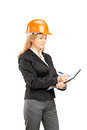 Female architect with a helmet writing on a clipboard isolated white background Royalty Free Stock Photos