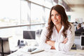 Female architect at her desk in an office, looking to camera Royalty Free Stock Photo