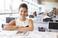 Female architect at her desk, smiling to camera Royalty Free Stock Photo
