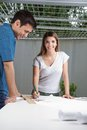 Female architect working on blueprint portrait of young with colleague standing by table Royalty Free Stock Photos