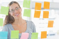 Female artist looking at colorful sticky notes concentrated the office Royalty Free Stock Photo