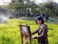 A female artist painting in rape field Stock Photo