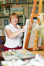 Female artist paints  on canvas in studio Stock Images
