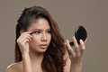 Female asian applying eye liner a with make up and pink shadow holding a liquid pen while looking at a mirror Royalty Free Stock Image