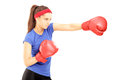 Female athlete hitting with red boxing gloves isolated on white background Stock Images