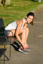 Female athlete lacing sport shoes before running in park and getting ready for outdoor training a woman tying footwear laces Royalty Free Stock Images