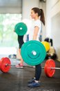 Female athlete lifting barbell at gym full length side view of Royalty Free Stock Photo