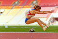 Female athlete makes long jump Royalty Free Stock Photo