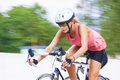 Female athlete riding bike outdoors young caucasian woman on the race panning technique used horizontal shot Royalty Free Stock Image