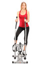 Female athlete standing on a cross trainer machine Royalty Free Stock Photography