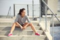 Female athlete taking a break from running sitting on the stairs Royalty Free Stock Photo