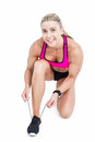 Female athlete tying her shoelace on white background Royalty Free Stock Image