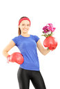 Female athlete wearing boxing gloves and holding a bunch of flow flowers isolated against white background Stock Image