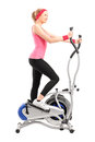Female athlete working on a cross trainer machine Royalty Free Stock Photography