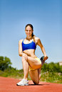 Female athletic stretching leg on sport track Royalty Free Stock Photography