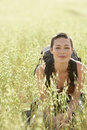 Female backpacker crouching in field of grass portrait young Stock Images